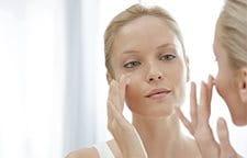 Žena nanosi kremu na lice
